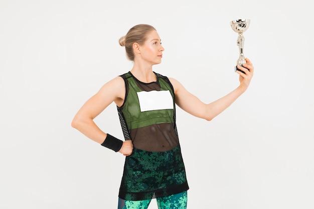スポーツウェアのスポーツ少女は灰色の背景にカップを保持しています。