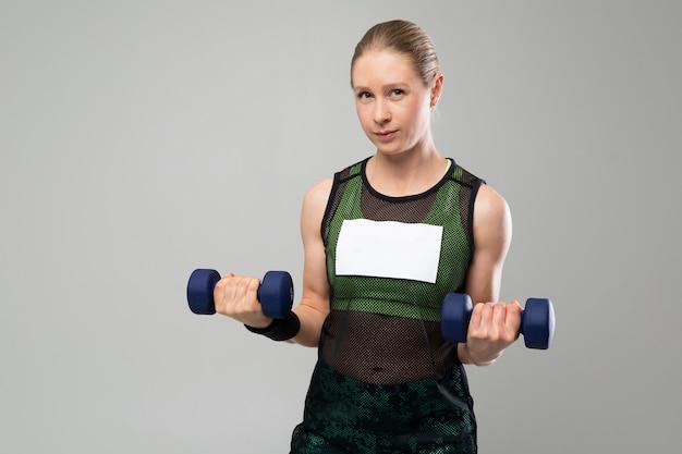 スポーツウェアで強いブロンドの女の子は灰色の背景にダンベルを保持します