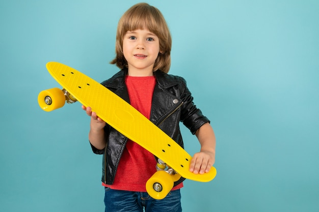 Мальчик держит желтый скейтборд в руках на синем фоне