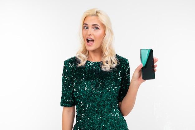 Блондинка в зеленом блестящем платье показывает пустой дисплей смартфона с макетом на белом фоне с копией пространства