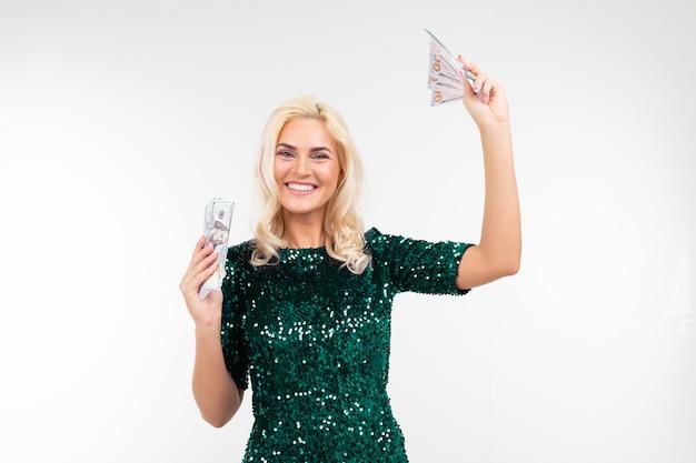 Счастливая очаровательная девушка в зеленом платье выиграла в лотерею и получила денежный приз на белом фоне с копией пространства