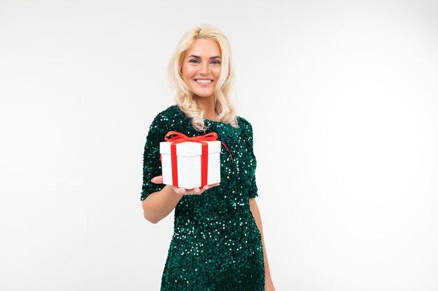 Счастливая играющая девушка в зеленом блестящем платье получила подарок на день рождения на белом фоне с копией пространства