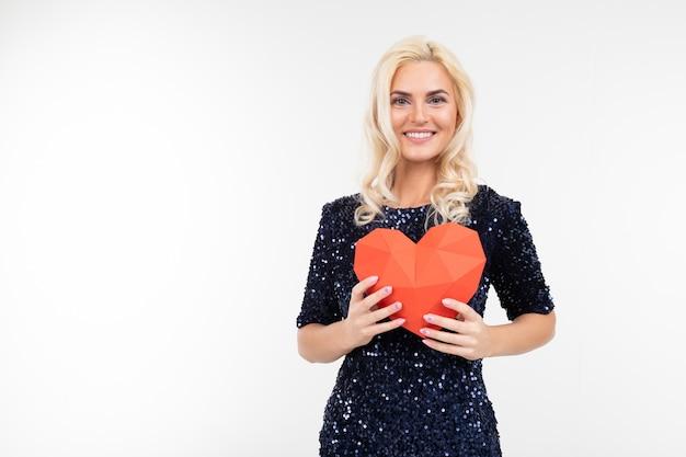 Белокурая молодая женщина в голубом платье держа бумажное красное сердце на белой предпосылке с космосом экземпляра