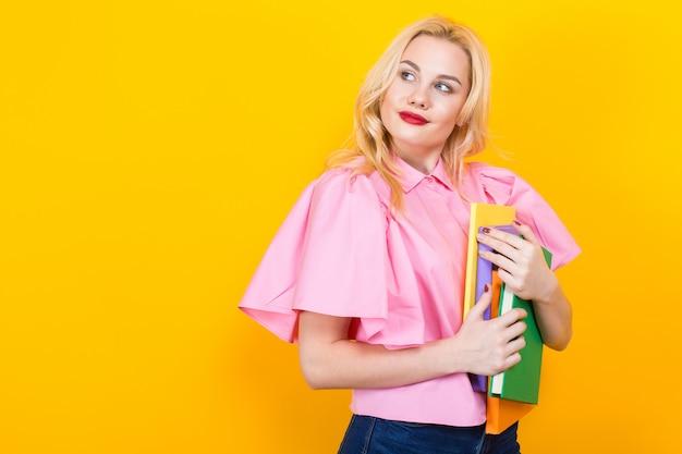本の山とピンクのブラウスで金髪の女性