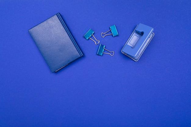 青色の背景に学校やオフィス用品がきちんと横たわっています