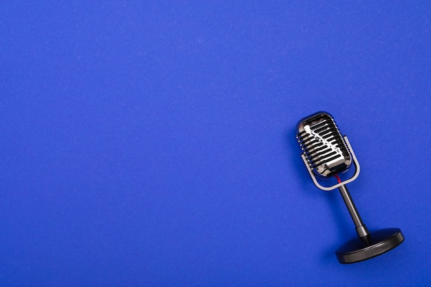 青の背景に分離された黒のマイク