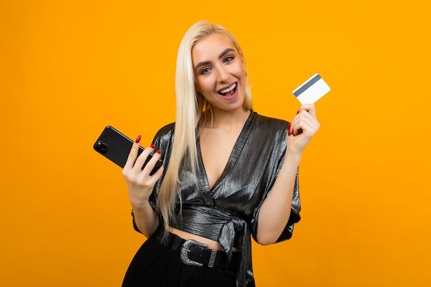 ヨーロッパの女の子は黄色のスタジオスペースに電話とモックアップ付きクレジットカードを保持しています。
