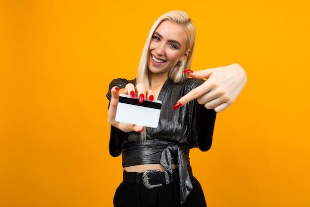 光沢のあるブラウスで魅力的なブロンドの女の子は、コピースペースを持つ孤立したオレンジスタジオスペースの銀行のためにモックアップでクレジットカードを保持しています。
