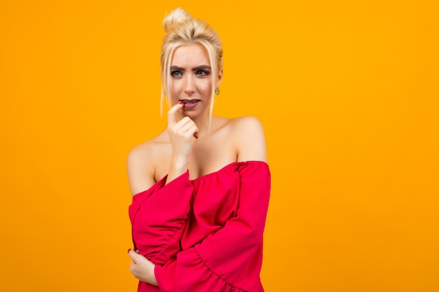 黄色のスタジオスペースに赤いドレスを着たセクシーな興奮しているブロンドの女の子