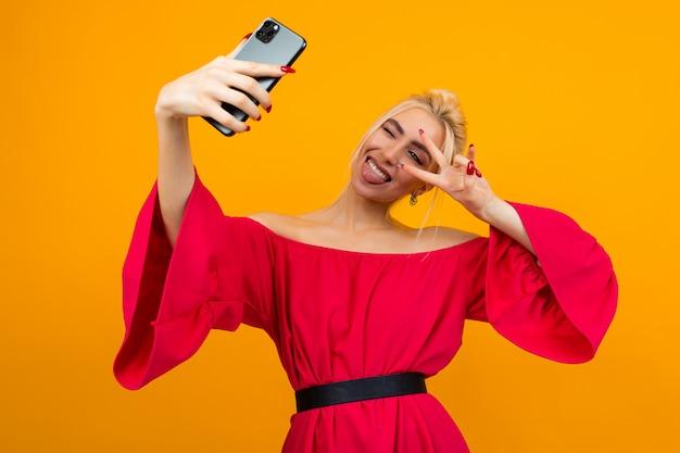 エレガントな赤いドレスを着た若い笑顔の女性は、黄色のスタジオスペースに電話で自分の写真を作る
