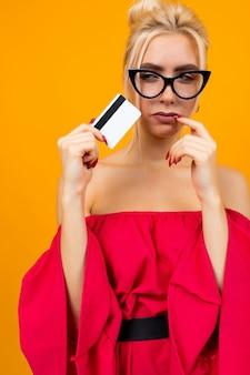 赤いドレスの魅力的な女の子は、黄色のスペースに銀行のレイアウトのクレジットカードを保持しています。