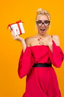 赤いドレスを着た嬉しい驚きの魅力的な若い女性がオレンジ色のスペースに赤い誕生日リボン付きの白いギフトボックスを受け取った