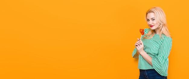 笑顔の金髪女性保持ハート型のロリポップ、背景