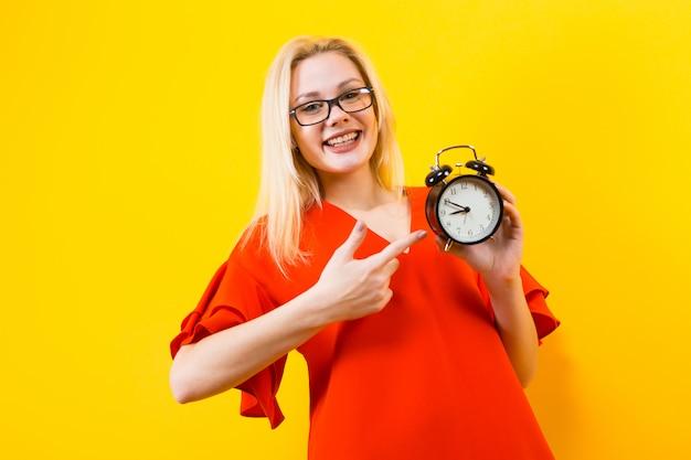 Блондинка держит будильник