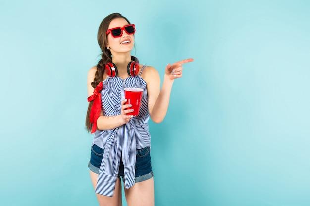 ヘッドフォンとカップを持つ若いセクシーな女性