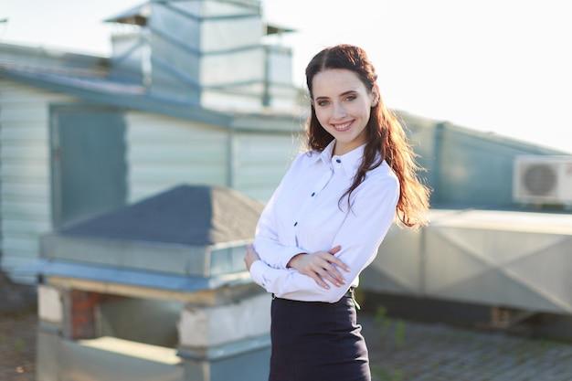 白いブラウスと黒いスカートの魅力的な女性実業家が屋根の上に立つ