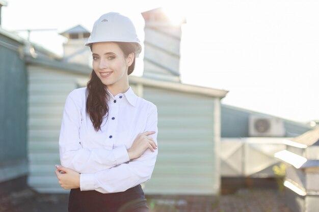 白いブラウス、ヘルメット、黒いスカートの魅力的な女性実業家が屋根の上に立つ