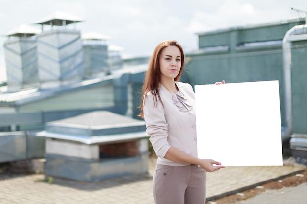 ベージュのスーツと茶色のズボンの格好良いビジネスレディーは屋根の上に立ち、空のプラカードを見せます
