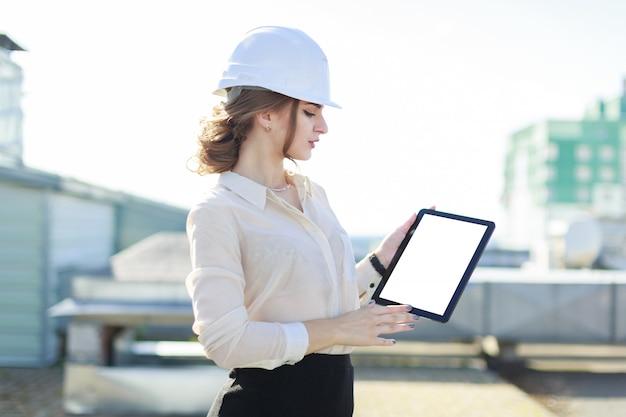 白いブラウス、時計、ヘルメット、黒いスカートの美しい女性実業家が屋根の上に立ち、空のタブレットを見せます