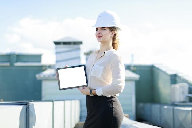 白いブラウス、時計、ヘルメット、黒いスカートの魅力的なビジネスレディが屋根の上に立ち、空のタブレットを見せます