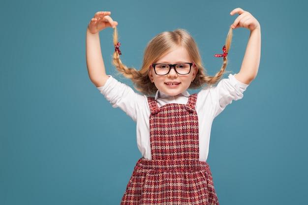 Милая маленькая девочка в красном платье, белой рубашке и очках
