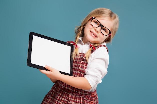 Милая маленькая девочка в красном платье, белой рубашке и очках держит пустой планшет