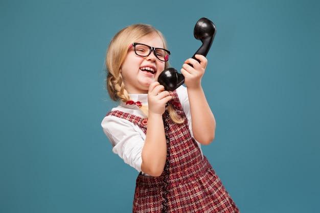 Очаровательная маленькая девочка в красном платье, белой рубашке и очках держит телефонную трубку