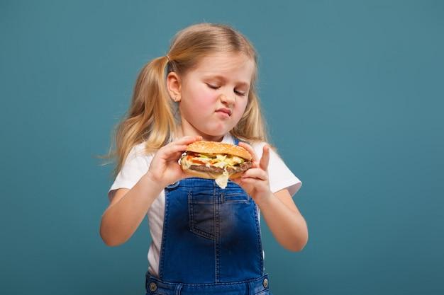 白いシャツとハンバーガーとジャンジャンプスーツで愛らしいかわいい女の子