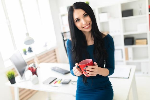 オフィスの若い女の子がテーブルに座って、赤カップを手に持っていました。