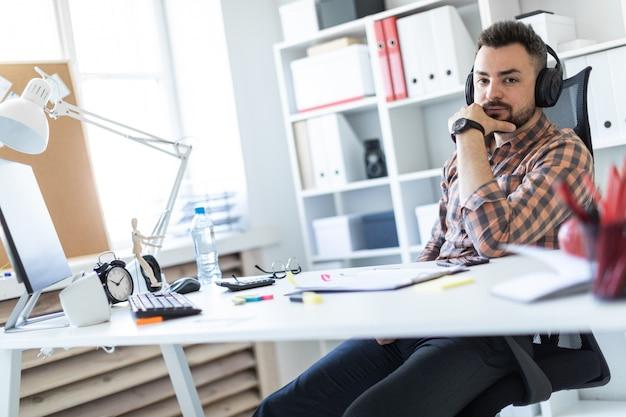 ヘッドフォンを着た若い男がオフィスのテーブルに座って、モニターを見ています。