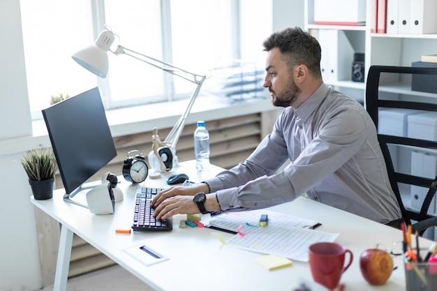 オフィスの若い男がテーブルに座って、ドキュメントとコンピューターを操作します。