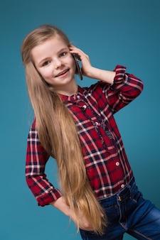 長い髪のシャツでかわいい女の子が携帯電話を保持します。