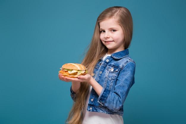 長い茶色の髪とジャンジャケットの小さなかわいい女の子がハンバーガーを保持します。