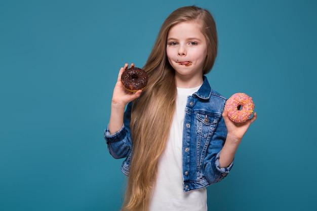 Красивая маленькая девочка в джинсовой куртке с длинными каштановыми волосами держит тесто