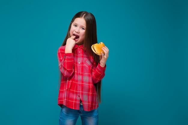 黒髪の市松模様のシャツでかわいい女の子がハンバーガーを保持します。