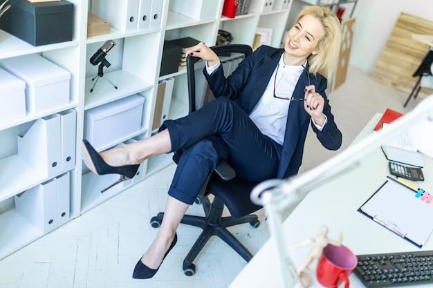 オフィスの若い女の子が椅子に座り、肘掛けに足を投げます