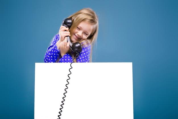 紫色のドレスのかわいい女の子が空の空白のプラカードと電話の受話器を保持します。