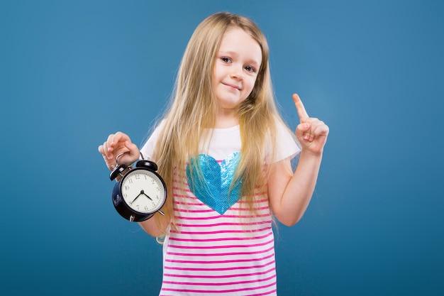 青いハートとジーンズと白いストライプシャツの愛らしい少女は目覚まし時計を保持します。