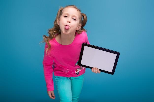 猿と青いズボンとピンクのシャツの美しい少女は、空のタブレットを保持します。