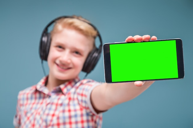 Подросток с наушниками показывает дисплей смартфона