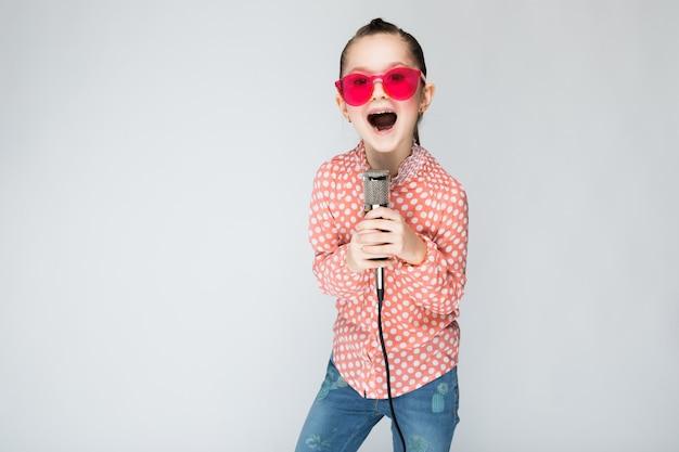 Девушка в оранжевой рубашке, очках и синих джинсах на сером