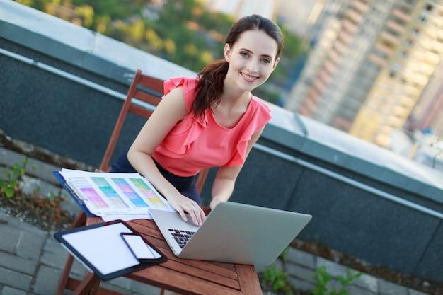 ピンクのブラウスの魅力的なビジネスレディーは屋根の上に座り、ラップトップで作業する