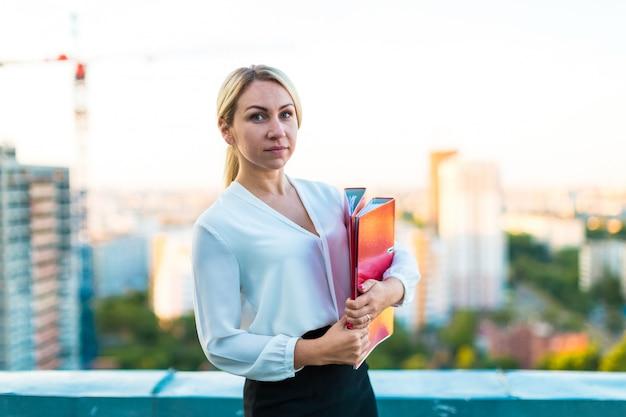 若い魅力的なビジネス女性の手で紙フォルダーと屋根の上に立つ