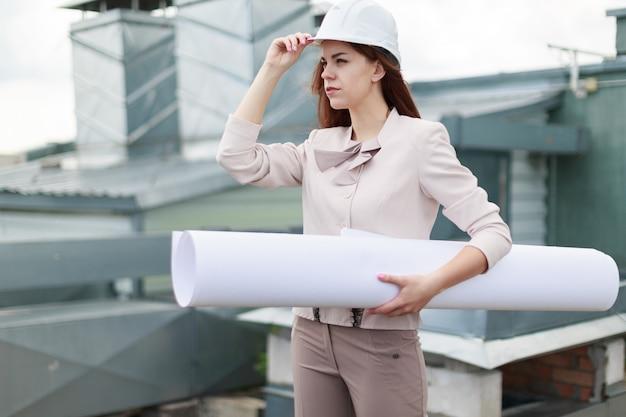 ベージュのスーツの魅力的な女性実業家は屋根の上に立ち、書類を保持