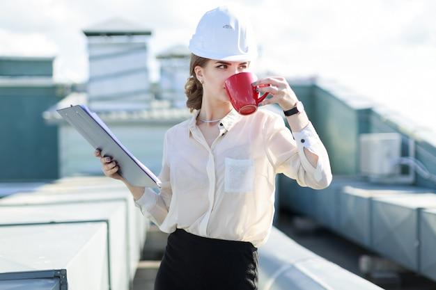 白いブラウス、時計、ヘルメット、黒いスカートの魅力的な女性実業家が屋根の上に立って、タブレットとコーヒーカップを保持