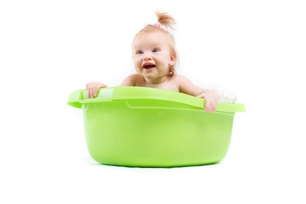 かわいい赤ちゃんの女の子は緑の浴槽でお風呂