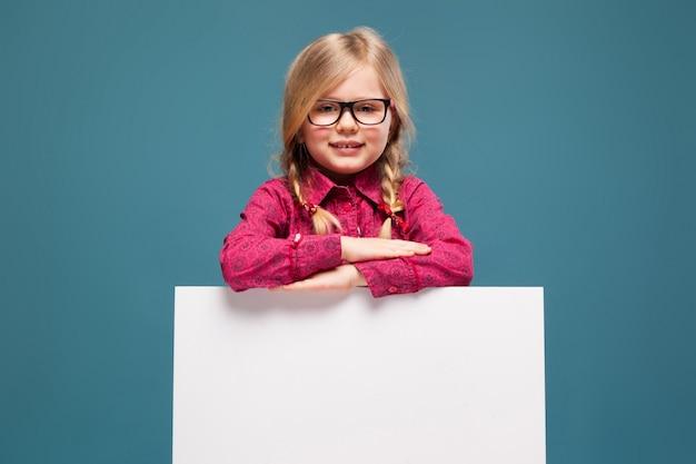 ピンクのシャツ、黒いズボン、メガネの愛らしい少女は、空の空白のプラカードを保持しています