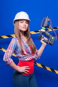 市松模様のシャツ、白いヘルメット、ジーンズの若いセクシーな労働者の女の子が釘銃で立つ