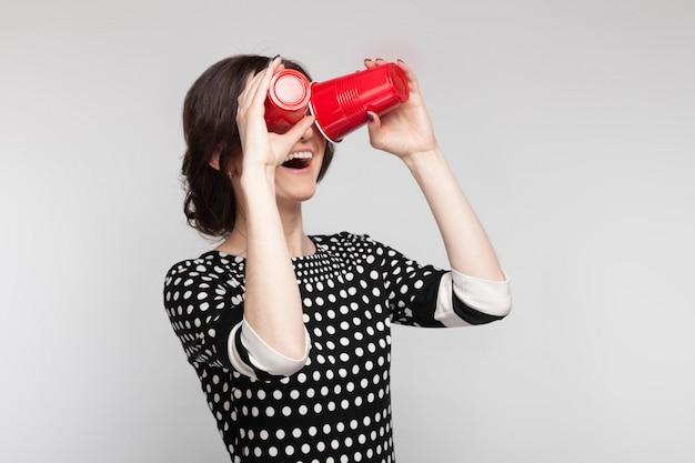Картина привлекательная женщина в крапчатой одежде, стоя с чашкой в руках