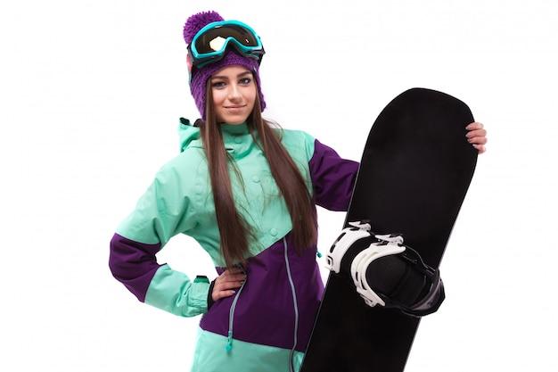 紫のスキーコートとゴーグルの若い美しい女性がスノーボードを保持します。